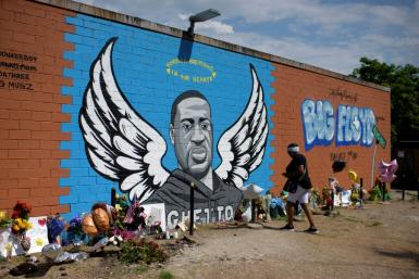 Visitors pay their respects to George Floyd in front of a mural in Houston, Texas on Monday, June 8, 2020