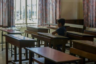 A Lebanese pupil looks out of the window of his empty classroom at Our Lady of Lourdes school, a century-old establishment in the city of Zahle that is due to close because of Lebanon's worst economic crisis sine the 1975-1990 civil war