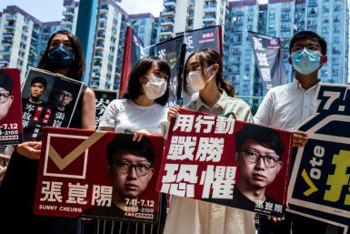 Joshua Wong (R) and fellow pro-democracy activists campaign during the primary which was held despite a warning that it could be in breach of a tough new security law imposed by Beijing