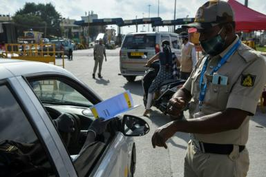 Police stop people travelling to Bangalore and direct them to undergo coronavirus screening as the Indian IT hub imposes a fresh lockdown in an attempt to contain a surge of infections