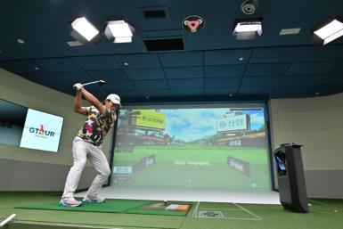 A South Korean golfer hits in a simulation booth during the GTour screen golf tournament in Daejeon, south of Seoul