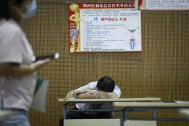 A jobseeker takes a break at a recruitment fair in Zhengzhou, China. Young graduates face a tough employment market