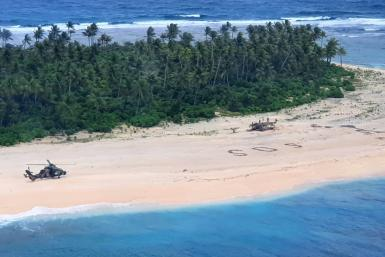 """A photo taken by the Australian Defence Force shows an army ARH Tiger helicopter landing near the letters """"SOS"""" on Pikelot Island"""