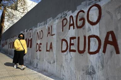 """A woman passes by a wall reading """"No to the Debt Payment"""" in Buenos Aires, on August 3, 2020 -- the day before a deal was reached on restructuring of $66 billion of debt"""