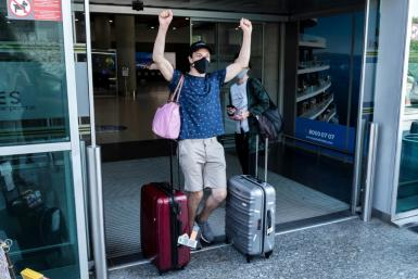 A traveller, mask-clad due to the COVID-19 coronavirus pandemic, arriving on one of the first flights from Britain gestures as he walks with luggage out of the terminal at Cyprus' Larnaca International Airport on August 1