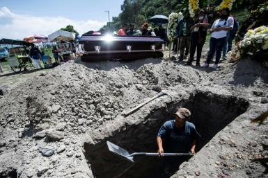 A grave is dug while a family waits during a funeral for a COVID-19 victim at the San Miguel Xico cemetery in Mexico