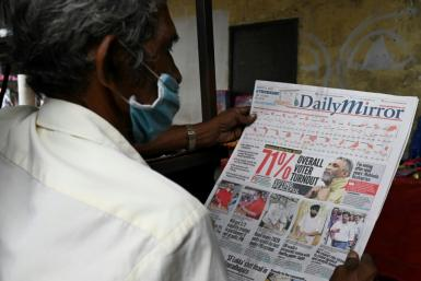 A man reads a newspaper in Colombo a day after Sri Lanka's parliamentary polls saw a turnout of over 70 percent