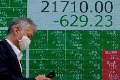 A man walks past a board displaying share prices in Tokyo
