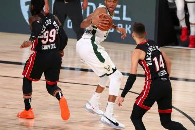 Milwaukee Bucks forward Giannis Antetokounmpo, center, moves the ball against Miami's Jae Crowder, left, and Tyler Herro in a 130-116 victory Thursday that clinched a top seed for the NBA playoffs for the Bucks