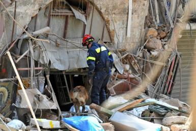 A French rescuer uses a sniffer dog to search for survivors amidst the rubble of a building in Beirut's Gemayzeh neighbourhood two days after a colossal explosion devastated large swathes of the city centre