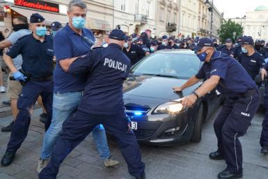 Police officers remove LGBT activists from blocking the road to a police vehicle transporting detained gay-right activist Margo in Warsaw, Poland