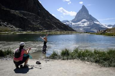 A tourist poses for a picture in the Riffelsee mountain lake with the Matterhorn mountain in background above the resort of Zermatt as heatwave sweeps across Europe