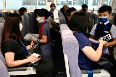 Children act as flight attendants in a mock cabin before a sightseeing 'flight to nowhere' later in the day