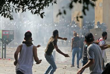 Lebanese protesters hurl rocks towards security forces during clashes in downtown Beirut