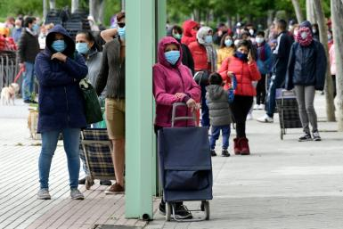 People queue for supplies from a food bank in Madrid on May 16, 2020. In late May, Spain rushed to launch a minimum basic income scheme due to the pandemic which has hit the country hard and devastated the economy