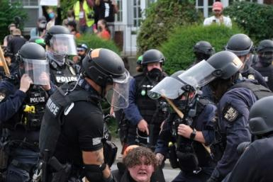 Riot police arrest protesters in Louisville after charges were announced in the Breonna Taylor case