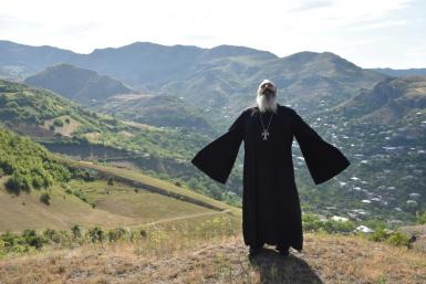 Priest Ter Abel prays for peace outside the village of Movses on the Armenian-Azerbaijani border on July 15, 2020