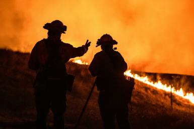 Firefighters keep watch on an approaching fire line on the outskirts of Santa Rosa, on September 27, 2020: the wildfire quickly spread over the mountains and reached Santa Rosa where it has begun to affect homes.