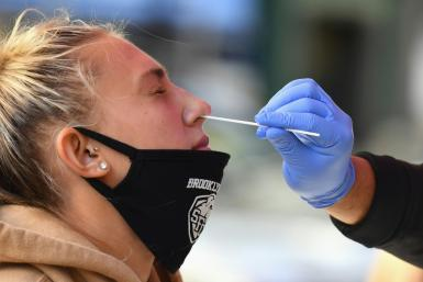 A medical worker takes a nasal swab sample from a student to test for COVID-19 in New York City.
