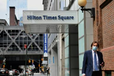 A pedestrian passes by New York's Hilton Times Square, which has closed due to the coronavirus pandemic