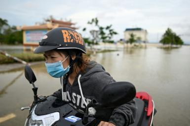 A woman pushes her scooter along a flooded road in Quang Dien district in central Vietnam's Hue province