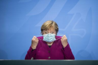 German Chancellor Angela Merkel takes her face mask off for a press conference after a meeting with the leaders of Germany's federal states on the coronavirus situation at the Chancellery in Berlin on Wednesday.