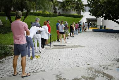 Americans wait in line to cast their ballots in Miami Beach on Florida's first day of early voting, barely two weeks before the tense US presidential election on November 3, 2020