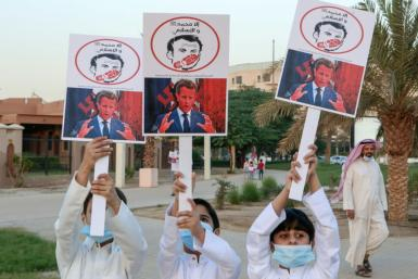 Kuwaiti youths brandish placards expressing anger at French President Emmanuel Macron