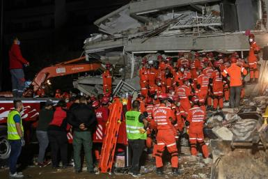 Rescuers search for survivors among the rubble of a collapsed building after a powerful earthquake struck Turkey's west coast and parts of Greece
