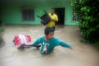 A boy and a man save chairs from a flooded house as heavy rains from tropical depression Eta cause flooding in Izabal, north of Guatemala City in November 2020