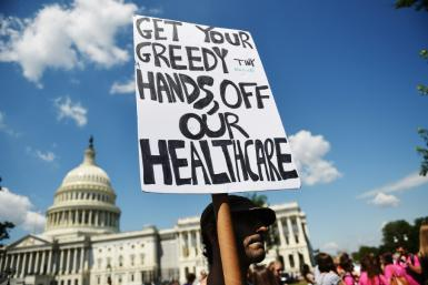 A protester holds a sign during a demonstration opposing the repeal of the Affordable Care Act