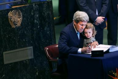 Former US secretary of state John Kerry signs the Paris climate accord at the UN building in New York, with his granddaughter Isabel Dobbs-Higginson seated on his knee