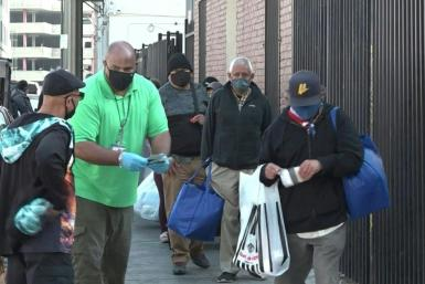 "IMAGES AND SOUNDBITESDespite the Covid-19 pandemic, the Los Angeles Mission maintains it's annual food distribution to help nourish those struggling to make ends meet this Thanksgiving. ""A hot meal, it warms your heart,"" says one beneficary."