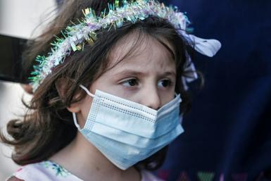 A Palestinian girl waits for a bride while wearing a protective mask due to the COVID-19 pandemic. To contain the spread of coronavirus, the Hamas Islamist group has banned large indoor gatherings