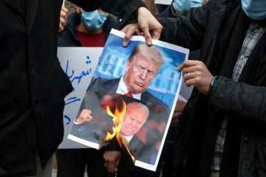 Students in Tehran burn posters depicting US President Donald Trump ( and President-elect Joe Biden during a rally on November 28, 2020 to protest the killing of nuclear scientist Mohsen Fakhrizadeh