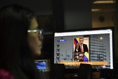 A journalist follows live a 2019 online encounter between Colombian President Ivan Duque and Venezuelan opposition leader Juan Guaido from a computer in Caracas, where the United States accuses China of helping restrict the internet