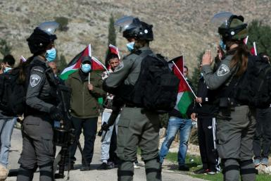 Palestinian demonstrators face Israeli forces during a protest against Israeli settlements in Kafr Malik in the occupied West Bank on December 4, 2020, the same day a Palestinian teenager was killed in clashes in the village of Mughayir