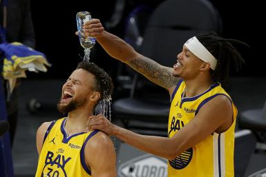 Stephen Curry #30 of the Golden State Warriors is showered in water by Damion Lee #1 of the Golden State Warriors