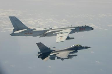 A handout photo taken and released on February 10, 2020 by Taiwan's Defence Ministry shows a Taiwanese F-16 fighter jet (bottom) flying next to a Chinese H-6 bomber