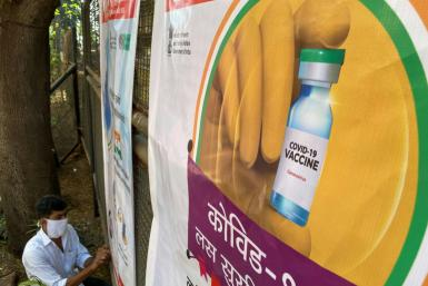 A worker sets up a poster at a coronavirus vaccination centre in Mumbai on January 15, 2021, with the Indian government aiming to inoculate around 300 million people by July