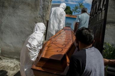 Workers remove the body of a Covid-19 victim in Brazil, which has seen a spike in infections
