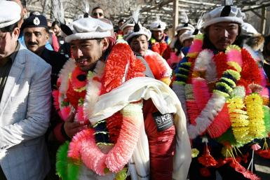 Nepali climbers Nirmal Purja and Mingma Sherpa are festooned with garlands on their arrival in Shigar district after conquering K2