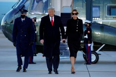 Outgoing US President Donald Trump and First Lady Melania Trump walk from Marine One at Joint Base Andrews in Maryland on January 20, 2021