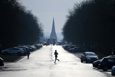 A jogger runs across a road in Greenwich Park in south east London on January 23, 2021. England has been in a third nationwide lockdown since early this month