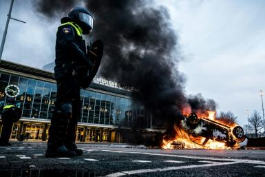 A car was torched outside Eindhoven's central train station where businesses were also looted