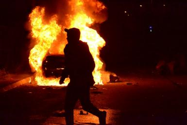 A protester runs past a burning vehicle during clashes with the army in Lebanon's impoverished second city Tripoli