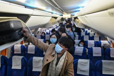 Passengers wearing protective facemasks as a preventive measure against Covid-19 leave a plane upon their arrival at the Tianhe International Airport in Wuhan, China