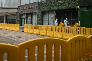 Workers wearing protective gear are seen in the compounds of The Jade Boutique Hotel, where members of the World Health Organization team did theiur quarantine