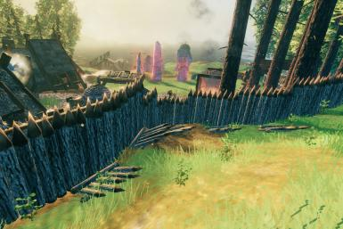 A row of log walls lined with a few spikes protecting a player's home in Valheim