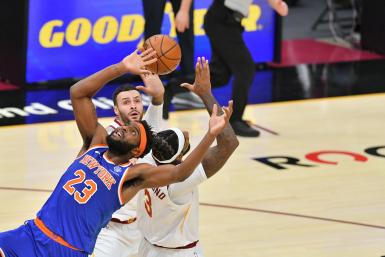 Mitchell Robinson #23 of the New York Knicks fights for a rebound over Andre Drummond #3 and Larry Nance Jr. #22 of the Cleveland Cavaliers
